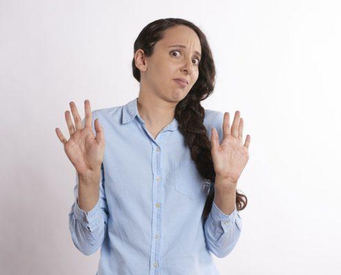 Frau hebt unschuldig Hände von sich weg