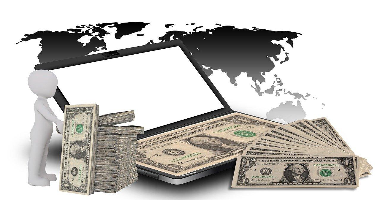 Laptop mit Geldscheinen auf Tastatur