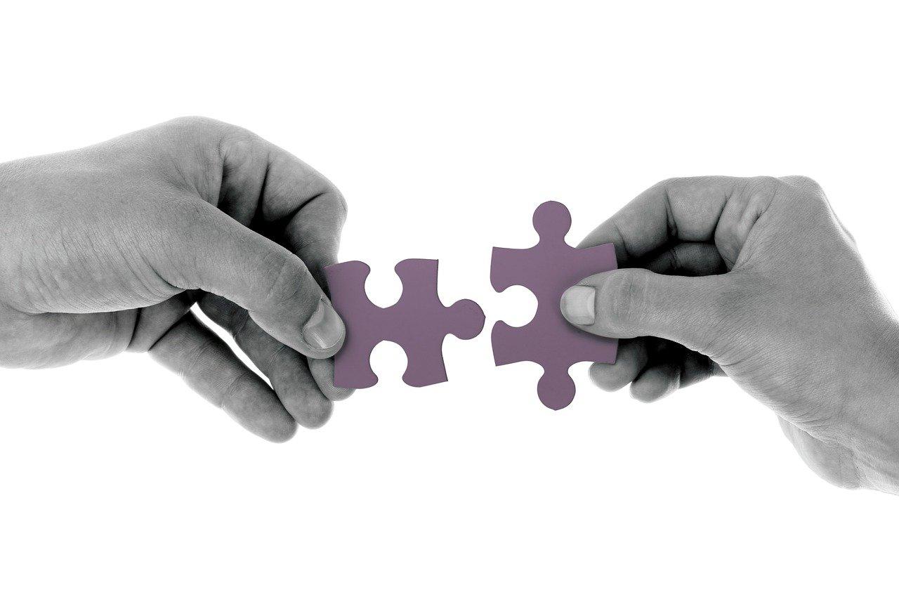Conversion und Traffic, 2 Hände strecken sich passende Puzzleteile entgegen