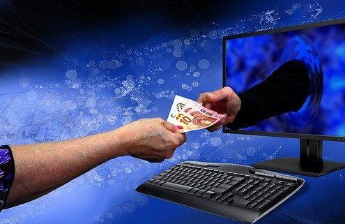 Conversionrate und Traffic, Hand streckt anderer Hand durch Bildschirm Geldscheine entgegen